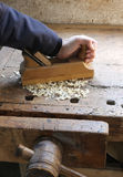 Carpenter's hand in the carpentry workshop with a plane Royalty Free Stock Photos