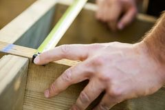 Carpenter's Hand Measuring Wood With Tape Royalty Free Stock Photo