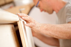 Carpenter's hand placing a board. Focus on the robust hand of a carpenter placing a flap (a wooden board) on a piece of a handcrafted wooden piece of furniture Royalty Free Stock Photos