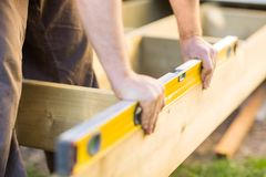 Carpenter's Hands Checking Level Of Wood At Site Royalty Free Stock Images