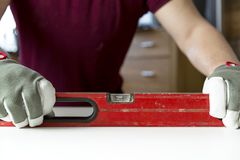 Carpenter`s hands checking level of wooden table at home. DIY projects, handyman. Carpenter`s hands checking level of wooden table at home. DIY projects royalty free stock image