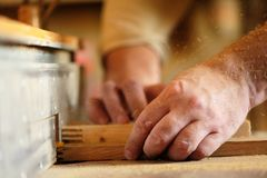 Carpenter's hands cutting piece of wood by cutter Royalty Free Stock Photos