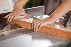 Carpenter's Hands Cutting Wood With Tablesaw Royalty Free Stock Photo