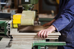 Carpenter's hands cutting wooden window frame. Close up of Carpenter's hands cutting wooden window frame with tablesaw in workshop stock image