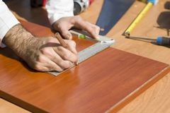 The carpenter`s hands indicate the dimension on the board with a pencil and an angle. stock images