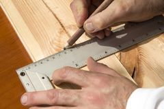 Carpenter`s hands indicate the dimension on the board with a pencil and an angle. The carpenter`s hands indicate the dimension on the board with a pencil and an stock image