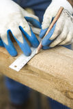 Carpenter`s hands in protective gloves indicate with a pencil the dimension with an angle. The carpenter`s hands in protective gloves indicate with a pencil the Royalty Free Stock Photos