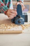 Carpenter's Hands Using Electric Planer On Wood. En plank in workshop Stock Photo