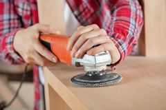 Carpenter's Hands Using Sander On Wooden Shelf Royalty Free Stock Photo