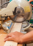 Carpenter`s hands on wood at table saw making a cut Stock Image