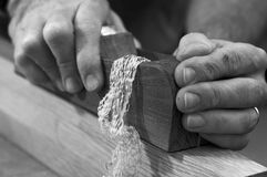 Carpenter's Plane with Shavings. Black and white close-up of woodworker's hands using a wood plane with shavings coming from the plane Stock Photos