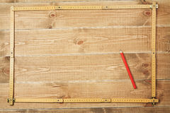 Carpenter's ruler and pencil. On a wooden planks Royalty Free Stock Image