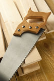Carpenter's saw. Is on a woode planks Royalty Free Stock Image