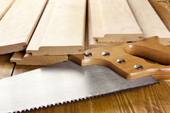 Carpenter's saw with wooden planks. Carpenter's saw is on a wooden planks Royalty Free Stock Photography