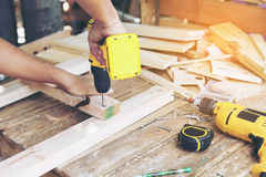Carpenter. Carpenter`s screwing a wood plate by wireless drill for make a chair, Diy at Home concept Stock Images