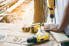 Carpenter. Carpenter`s screwing a wood plate by wireless drill for make a chair, Diy at Home concept Royalty Free Stock Images