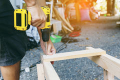 Carpenter. Carpenter`s screwing a wood plate by wireless drill for make a chair, Diy at Home concept Stock Image