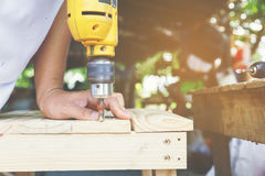 Carpenter. Carpenter`s screwing a wood plate by wireless drill for make a chair, Diy at Home concept Stock Photos