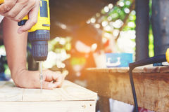 Carpenter. Carpenter`s screwing a wood plate by wireless drill for make a chair, Diy at Home concept Royalty Free Stock Photos