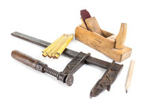 Carpenter's set. Basic set of carpenter's tools consisting of metal clamp, wooden folding ruler, plane and pencil all shot on white Stock Images