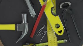 Carpenter's tools on a turntable. Hammer, nails,  blade knife, measuring tape, pencil, spirit level turnirg stock footage