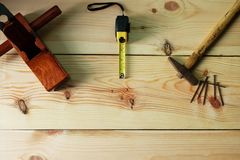 Carpenter`s for woodworking. Old Hammer and nail and wood plane and Measuring tape on texture wooden background stock image