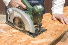 Carpenter`s workshop. Carpenter cuts the OSB Stock Photography