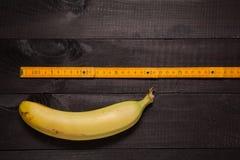 Carpenter's yellow ruler & banana Royalty Free Stock Image