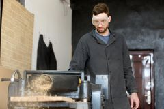 Carpenter in safety glasses works on machine tool. Carpenter in safety glasses standing near machine tool throwing out wooden sawdust while reducing thickness of Royalty Free Stock Images