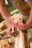 Carpenter with sanding block in carpentry Stock Image