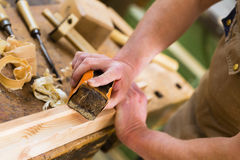 Carpenter with sanding block in carpentry Stock Images