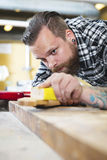 Carpenter sanding a guitar neck in wood at workshop Stock Photography
