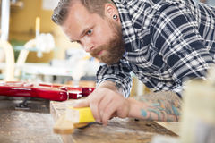 Carpenter sanding a guitar neck in wood at workshop Royalty Free Stock Photo
