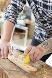 Carpenter sanding a guitar neck in wood at workshop Royalty Free Stock Image