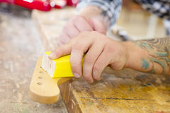 Carpenter sanding a guitar neck in wood at workshop Royalty Free Stock Image