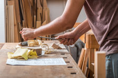 Carpenter sanding wood in the carpentry. In Germany Stock Image