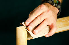 Carpenter man sanding wood molding for door frame Stock Images