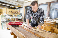 Carpenter sanding a wooden guitar neck in workshop Royalty Free Stock Photo