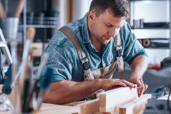 Carpenter sanding a wooden plank stock photography