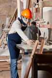 Carpenter with saw processing wood. At carpentry shop Royalty Free Stock Image
