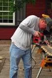 Carpenter sawing. Carpenter using a electric saw outdoors Royalty Free Stock Photography
