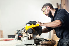 Carpenter sawing board with circular saw i stock images