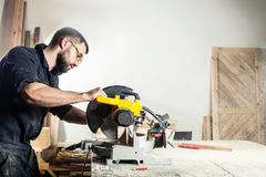 Carpenter sawing board with circular saw i. Young man builder carpenter sawing board with circular saw in workshop Royalty Free Stock Images