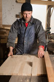 Carpenter sawing a board in the circulation saw. In a carpenter's workshop Stock Photography