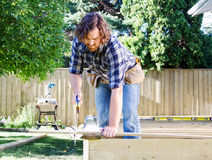 Carpenter sawing board. For deck royalty free stock photo