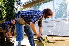 Carpenter sawing board for deck. Carpenter sawing board with skill saw royalty free stock images