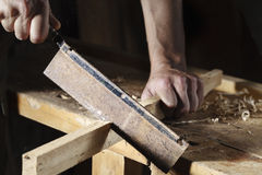 Carpenter sawing a board with a hand wood saw Stock Images