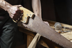 Carpenter sawing a board with a hand wood saw Royalty Free Stock Photos