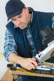 Carpenter sawing board on machine. Carpenter sawing a board on a machine Royalty Free Stock Photography