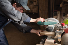 Carpenter sawing a board on a machine with a circulation saw. In the carpentry workshop Royalty Free Stock Photography